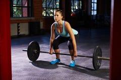 Женщина в спортзале подготавливая поднять весы стоковая фотография