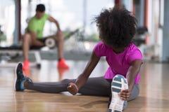 Женщина в спортзале протягивая и нагревая человека в worki предпосылки Стоковое Изображение RF