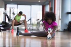 Женщина в спортзале протягивая и нагревая человека в worki предпосылки Стоковые Изображения RF