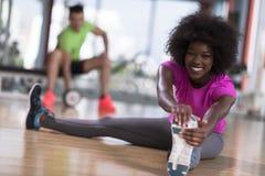 Женщина в спортзале протягивая и нагревая человека в worki предпосылки Стоковые Фотографии RF
