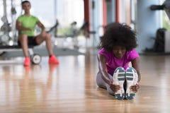 Женщина в спортзале протягивая и нагревая человека в worki предпосылки Стоковое Изображение