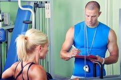 Женщина в спортзале работая с личным trai фитнеса Стоковое Изображение RF