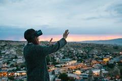 Женщина в стеклах виртуальной реальности на предпосылке захода солнца над городом Концепция будущих технологий самомоднейше Стоковые Изображения RF
