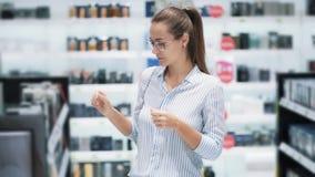 Женщина в стеклах выбирает духи в косметиках ходит по магазинам, обнюхивает ее, замедленное движение сток-видео