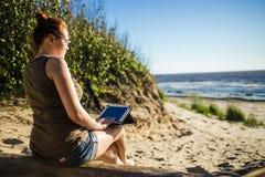 Женщина в стеклах используя цифровую таблетку на солнечном побережье песка моря независимом и концепции остатков Стоковое Изображение RF