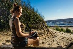 Женщина в стеклах используя цифровую таблетку на солнечном побережье песка моря независимом и концепции остатков Стоковое Фото