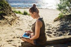 Женщина в стеклах используя цифровую таблетку на солнечном побережье песка моря независимом и концепции остатков Стоковая Фотография RF