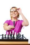 Женщина в стеклах показывая изолированного короля шахмат Стоковое Изображение