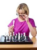 Женщина в стеклах рассматривает изолированного короля шахмат Стоковые Изображения