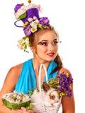Женщина в стиле пасхи держа кролика и цветков в корзине Стоковые Изображения RF