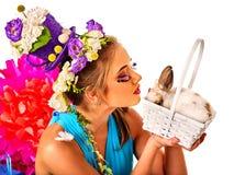 Женщина в стиле пасхи держа кролика и цветков в корзине Стоковая Фотография RF