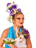 Женщина в стиле пасхи держа кролика и цветков в корзине Стоковое фото RF
