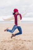 Женщина в стильной теплой одежде скача на пляж Стоковое Изображение RF