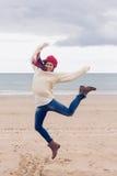 Женщина в стильной теплой одежде скача на пляж Стоковые Фотографии RF