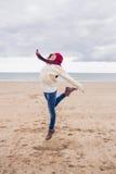Женщина в стильной теплой одежде скача на пляж Стоковая Фотография