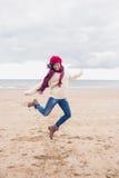 Женщина в стильной теплой одежде скача на пляж Стоковое фото RF