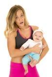 Женщина в стойке одежды фитнеса держа младенца стоковая фотография rf