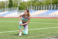 Женщина в страдании sportswear от боли колена стоковая фотография