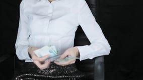 Женщина в стуле быстро подсчитывает валюшку денег, русские рублевки акции видеоматериалы