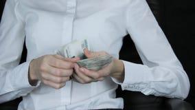 Женщина в стуле вскользь подсчитывает вне валюшку денег, русские рублевки видеоматериал