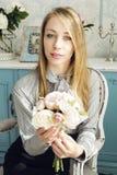 Женщина в стуле с цветками стоковое фото rf