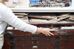 Женщина в студии гончарни извлекая материалы от комода плана Стоковые Фото