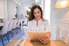 Женщина в таблетке чтения ресторана Стоковое Фото