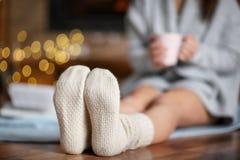 Женщина в теплых носках ослабляя дома стоковое фото rf