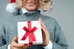 Женщина в теплых свитере и шляпе ` s santa держит подарок рождества Стоковые Фотографии RF