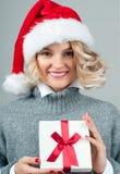 Женщина в теплых свитере и шляпе ` s santa держит подарок рождества Стоковые Изображения RF