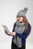 Женщина в ткани зимы используя планшет Стоковые Изображения