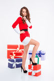 Женщина в ткани Санта Клауса показывая палец над губами Стоковые Изображения RF