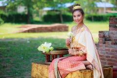 Женщина в традиционных одеждах складывает лепестки цветка лотоса используемые в ритуалах вероисповедания буддизма Лотос представл стоковое фото rf