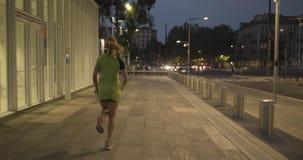 Женщина в тренировке носки фитнеса идущей на пешеходной дорожке Задний после взгляда Вечер или ноча лета промышленно сток-видео
