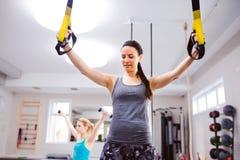 Женщина в тренировке спортзала подготовляет с прокладками фитнеса trx Стоковое Изображение