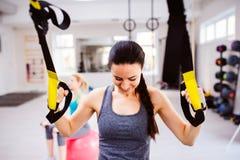 Женщина в тренировке спортзала подготовляет с прокладками фитнеса trx Стоковая Фотография RF