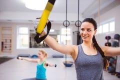 Женщина в тренировке спортзала подготовляет с прокладками фитнеса trx Стоковые Фотографии RF