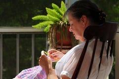 Женщина в тряся стуле используя вязание крючком Стоковое Фото