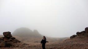 Женщина в туманном и высоком скалистом холме Стоковое Фото