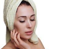 Женщина в тюрбане полотенца на белой предпосылке прикладывать политуру кожи внимательности прозрачную стоковая фотография rf
