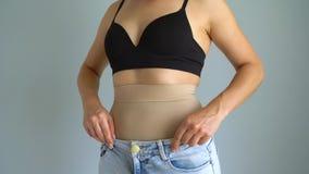 Женщина в уменьшении кальсон кладет джинсы на верхнюю часть и проверяет результат Концепция устремленности для совершенного тела акции видеоматериалы