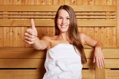 Женщина в удерживании sauna thumbs вверх Стоковые Фотографии RF