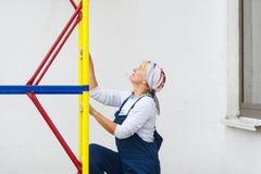 Женщина в форме построителя поднимает на лестницу конструкции Стоковые Фото