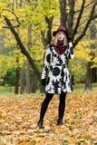 Женщина в флористической сделанной по образцу шляпе красного цвета пальто и вина в парке, рекой Счастливая девушка, красочный пор Стоковые Изображения RF