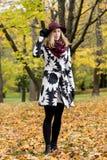 Женщина в флористической сделанной по образцу шляпе красного цвета пальто и вина в парке, рекой Счастливая девушка, красочный пор Стоковые Изображения