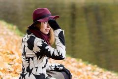 Женщина в флористической сделанной по образцу шляпе красного цвета пальто и вина в парке, рекой Счастливая девушка, красочный пор Стоковое Изображение