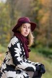 Женщина в флористической сделанной по образцу шляпе красного цвета пальто и вина в парке, рекой Счастливая девушка, красочный пор Стоковое Изображение RF