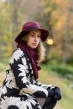 Женщина в флористической сделанной по образцу шляпе красного цвета пальто и вина в парке, рекой Счастливая девушка, красочный пор Стоковые Фотографии RF