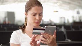 Женщина в ходить по магазинам авиапорта онлайн с кредитной карточкой на smartphone пока ждущ отклонение полета сток-видео