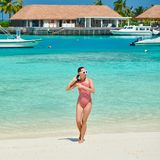 Женщина в цельном купальнике на пляже стоковые фото